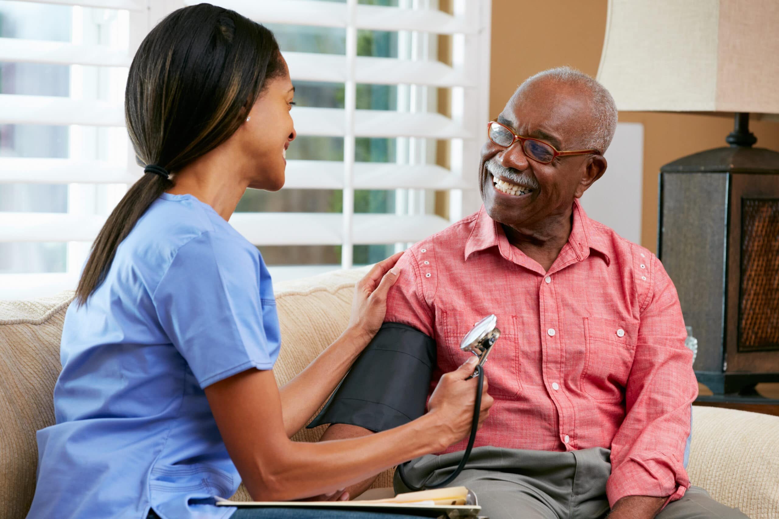 Physician taking blood pressure of elderly patient in living room of patient's home.