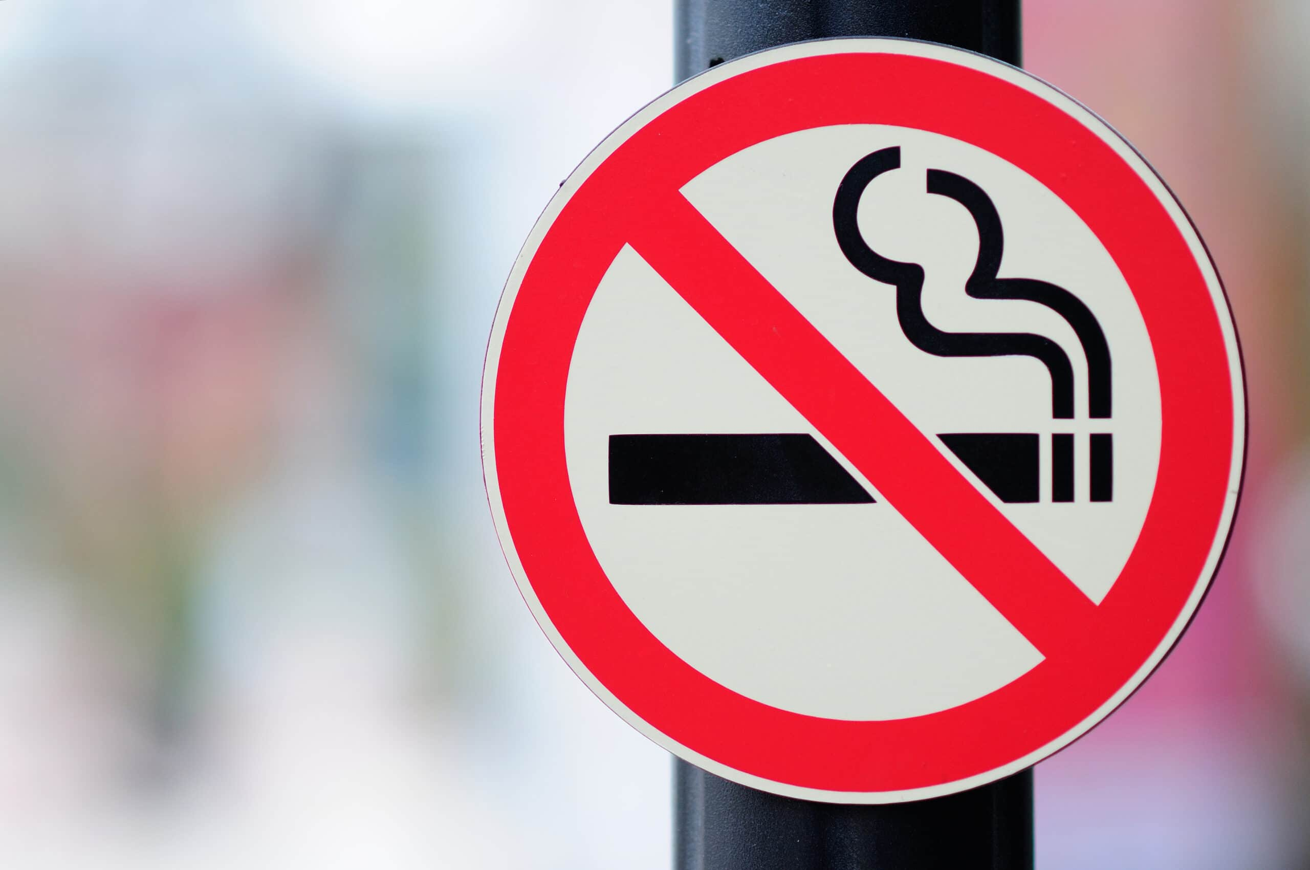 A red sign with a slash through a cigarette icon, indicating a no-smoking zone.