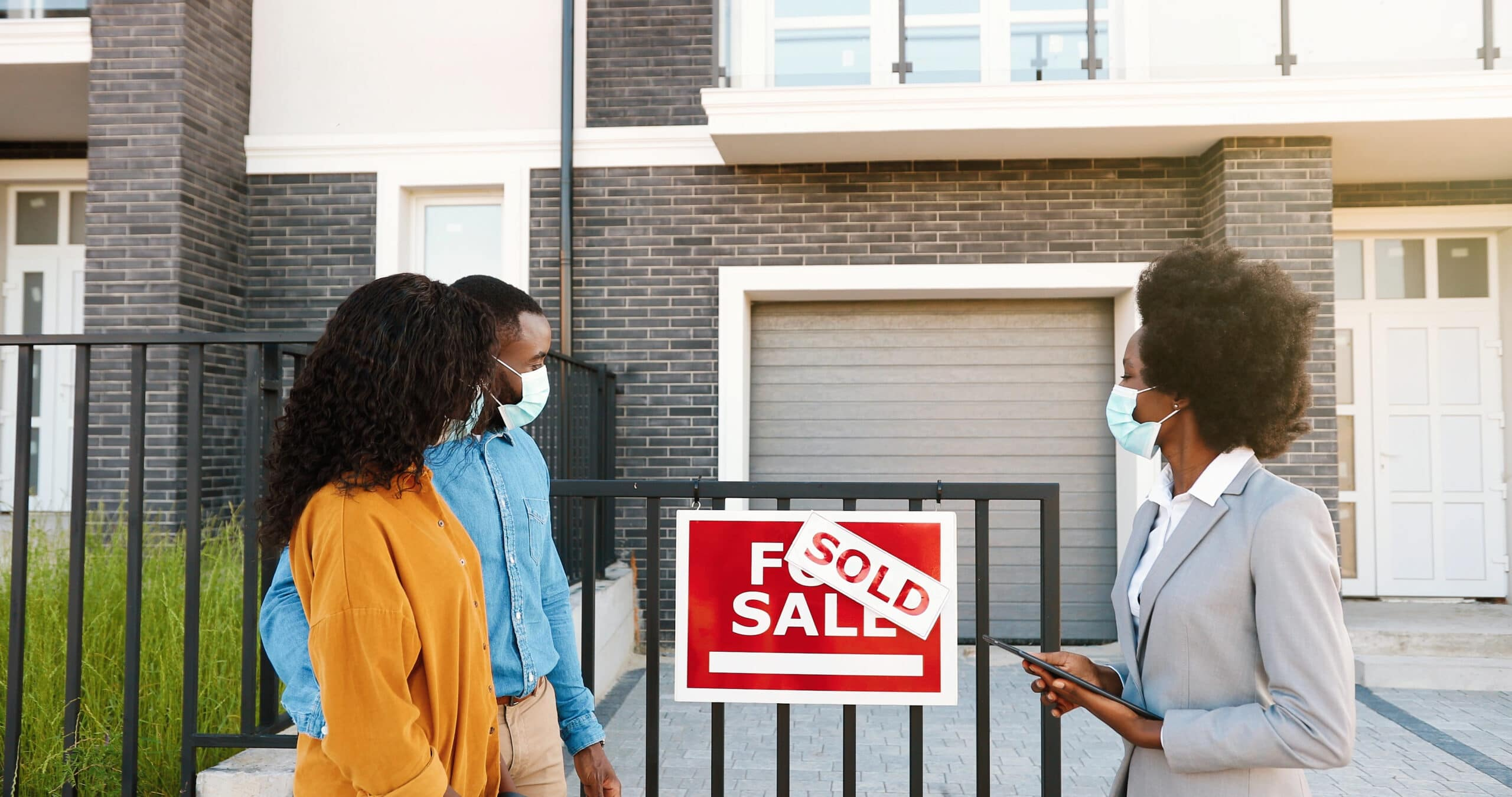 A couple and a real estate broker stand in front of a newly sold house.