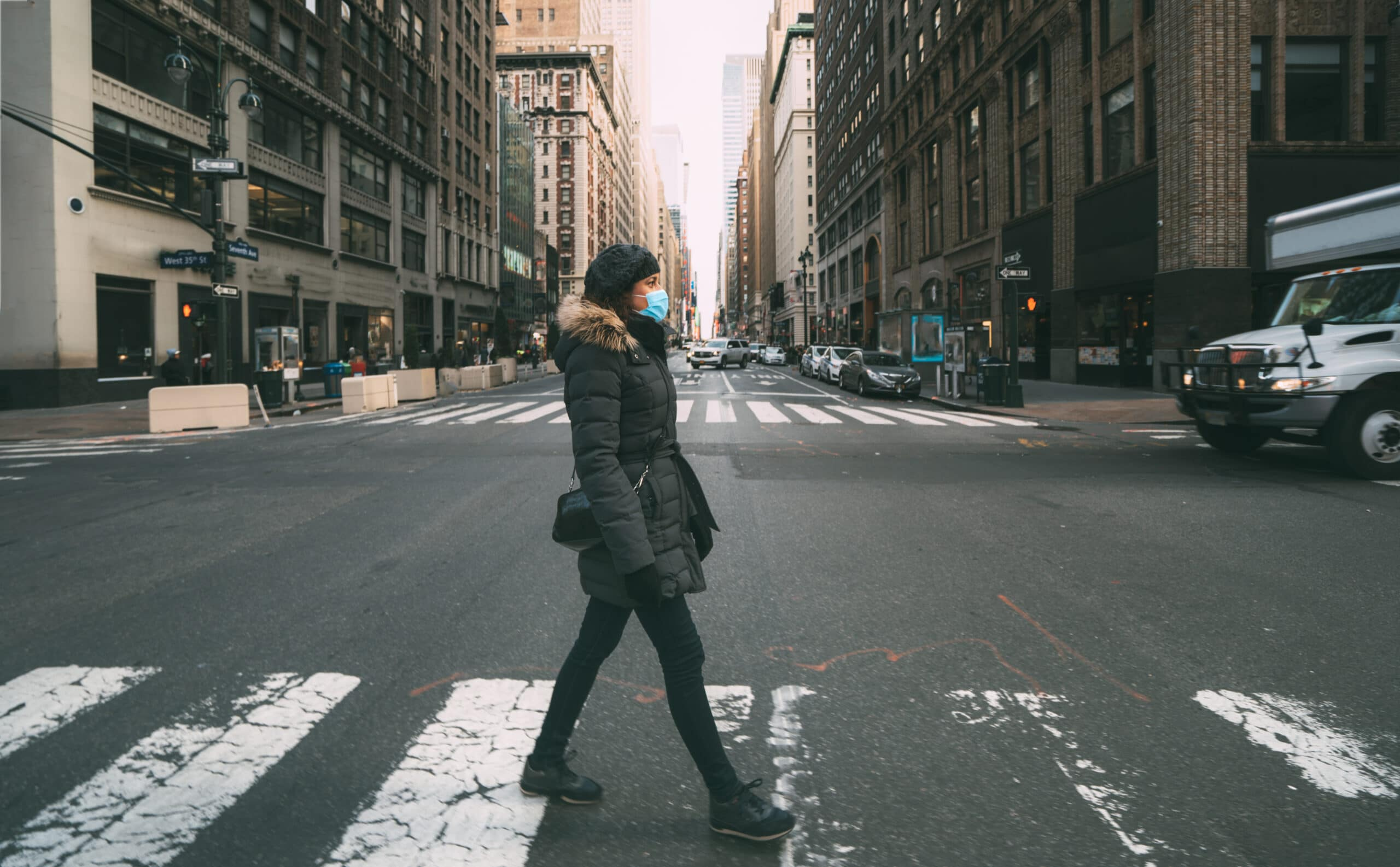 A woman wearing a face mask walks the city streets in New York.