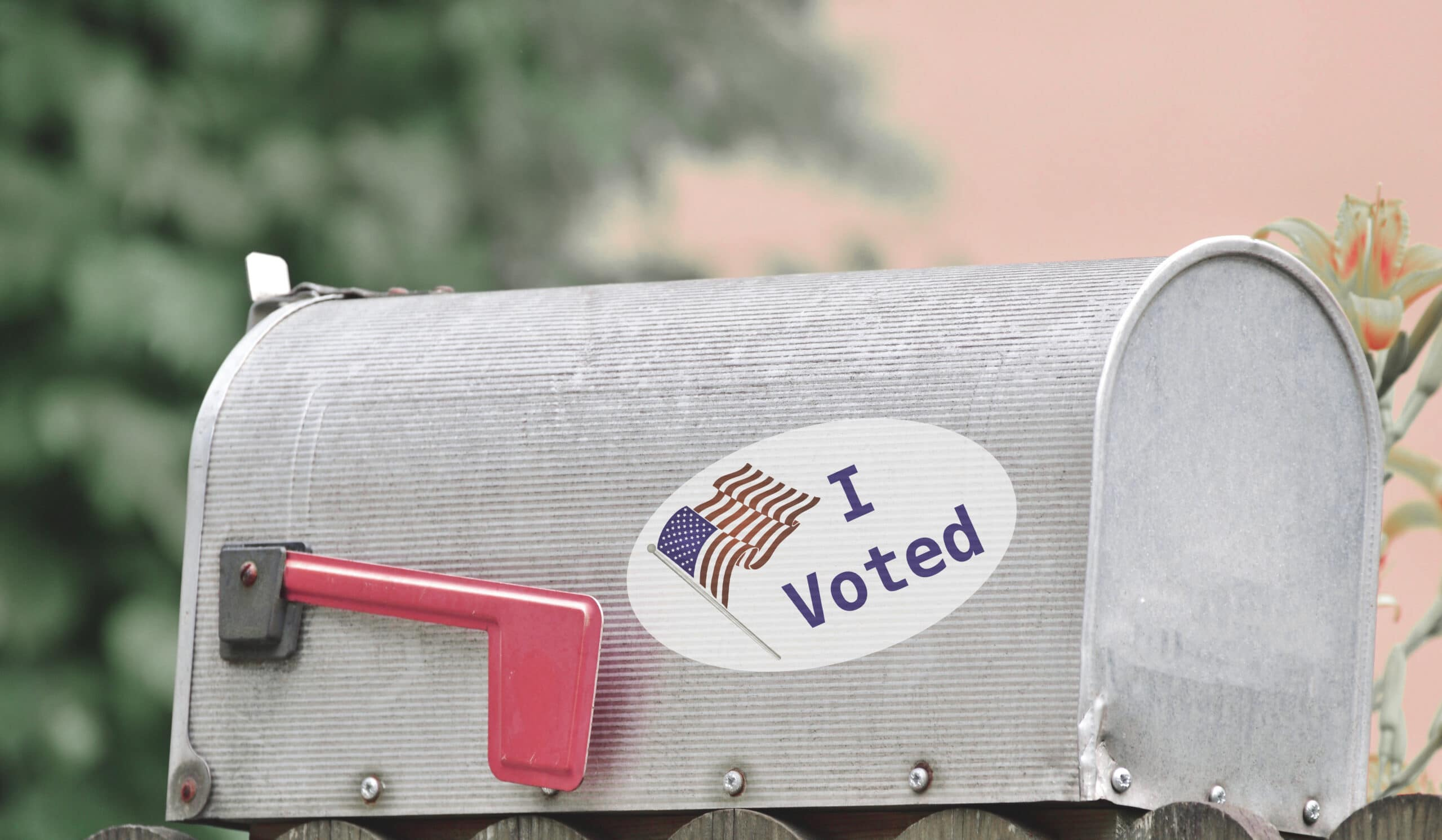 """A mailbox with an """"I Voted"""" sticker, showing this homeowner used a mail-in ballot to vote."""