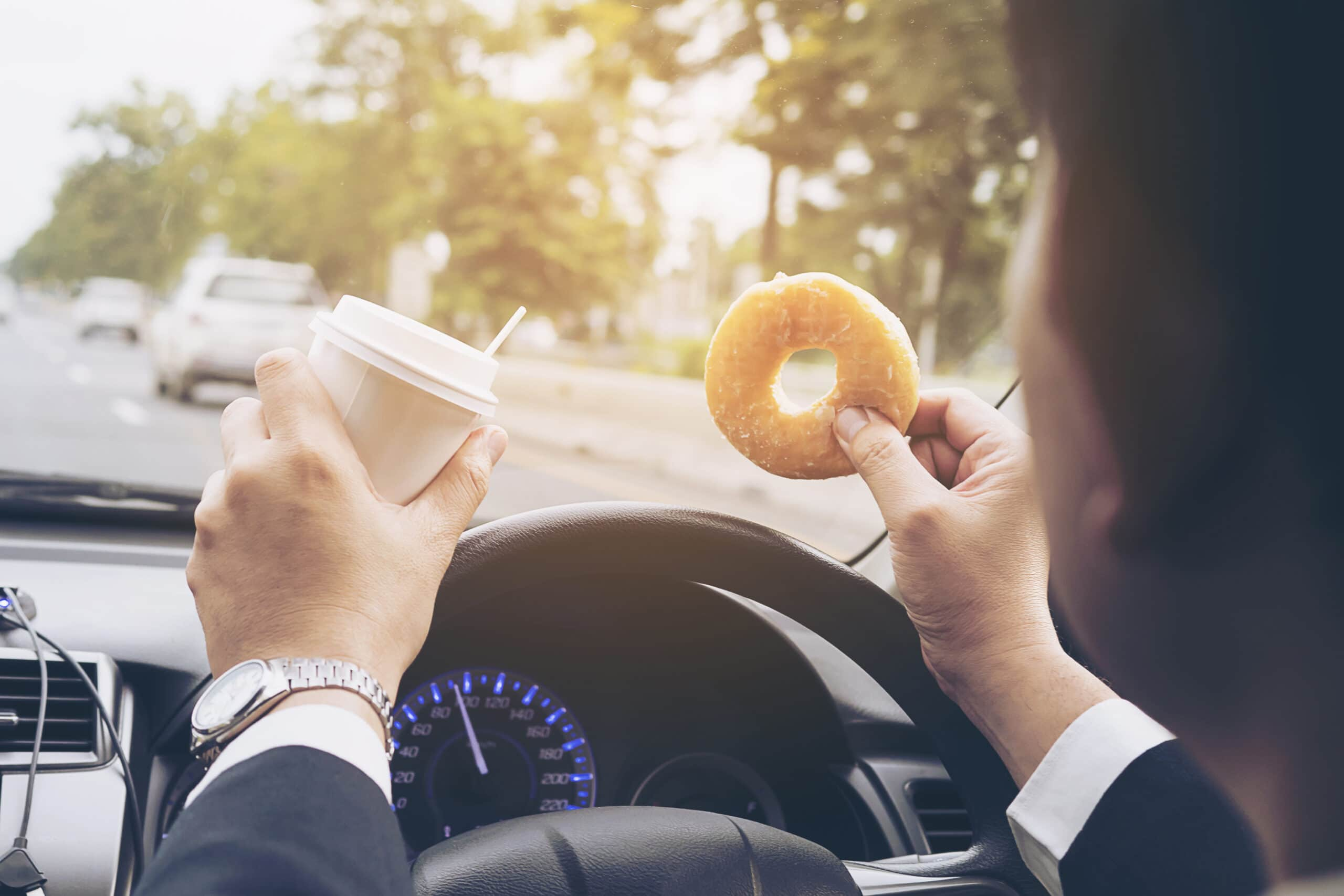 A man holds a portable coffee cup and donut while driving, indicating commute to work.