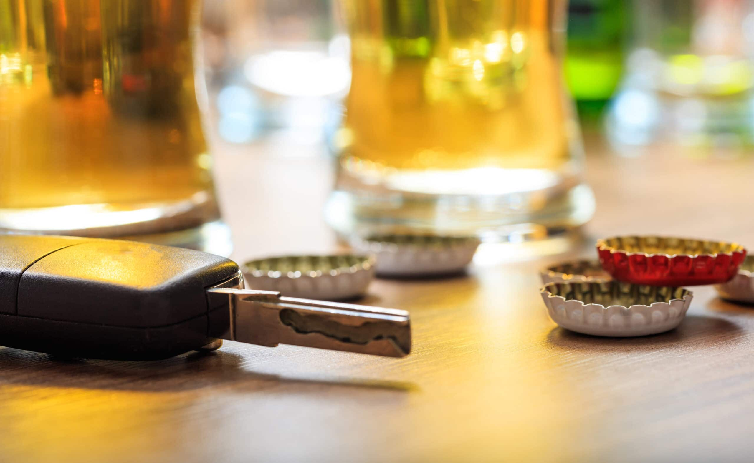 A car key is positioned next to beer bottle caps, implying the decision to drink and drive.