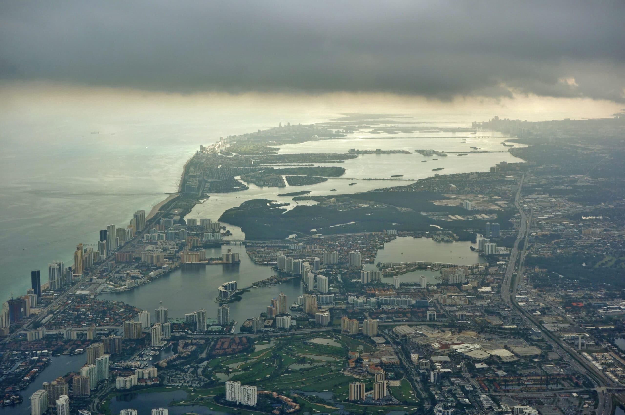 A dark cloud hovers over a coastal city in the United States, indicating climate change.