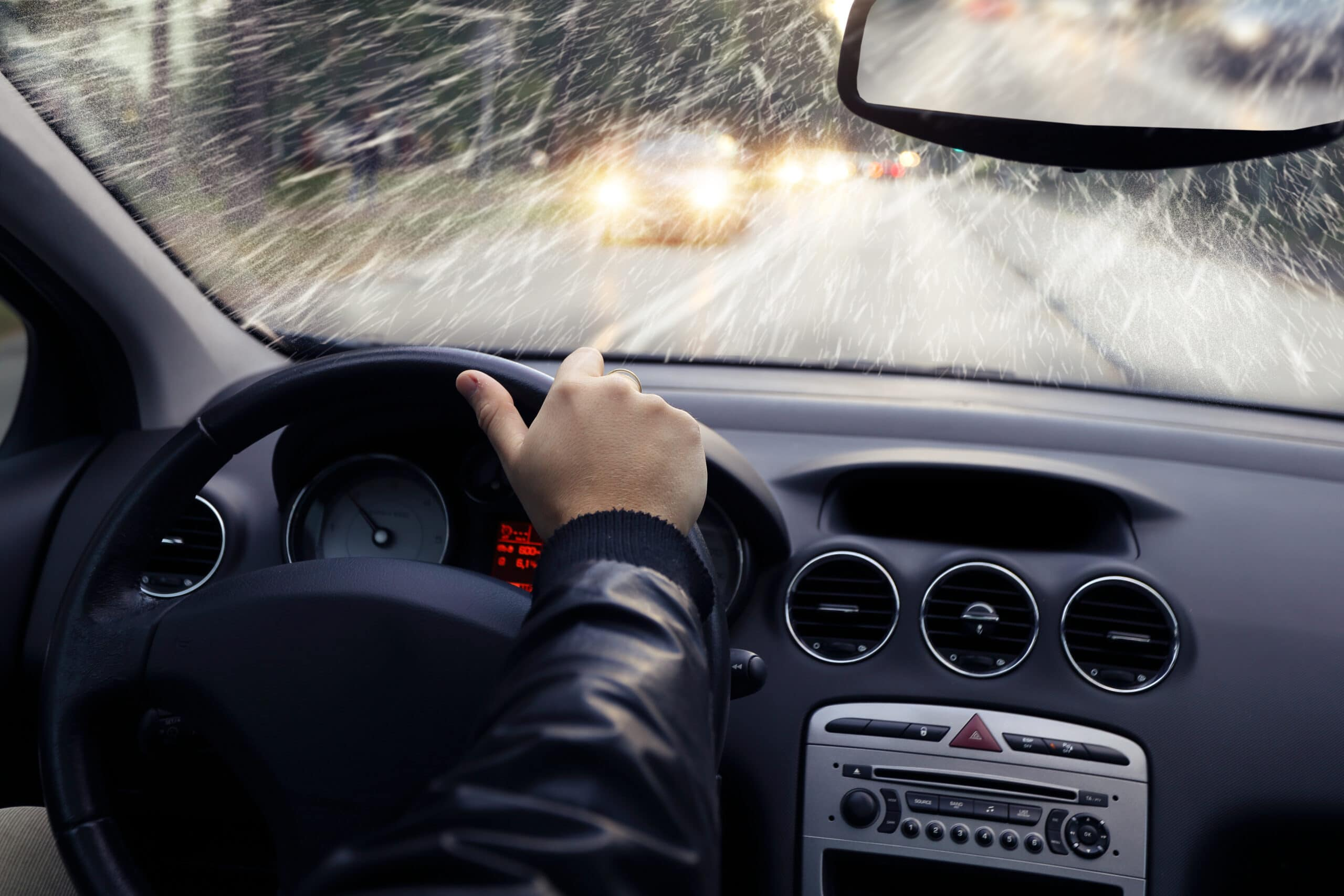 Driver navigates vehicle from behind the wheel in falling rain and snow