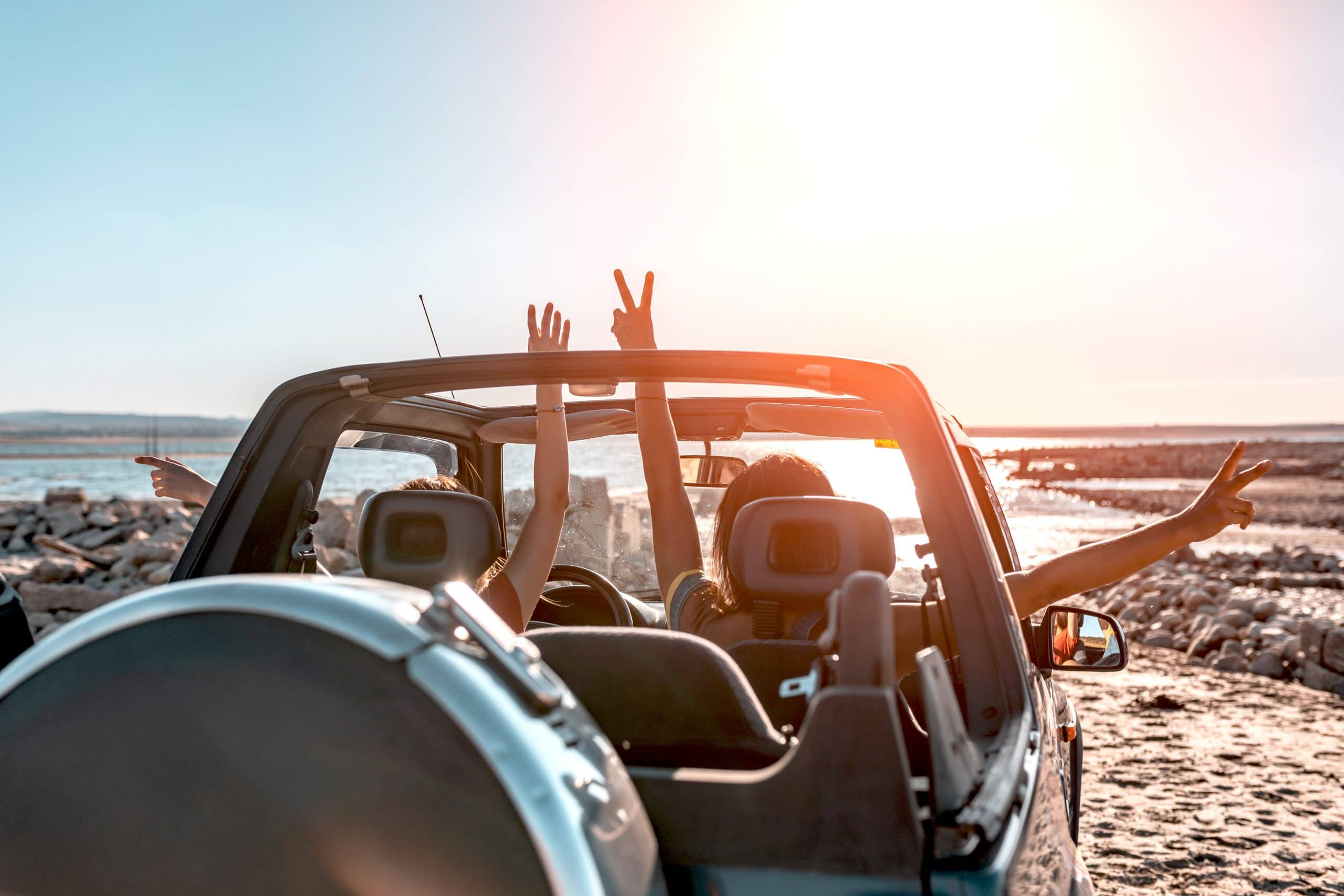 Two people in an open air Jeep celebrate with their hands in the air by the beach.
