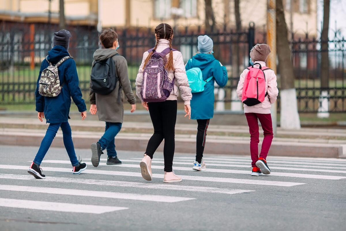 Children walking in a crosswalk on their way to school.